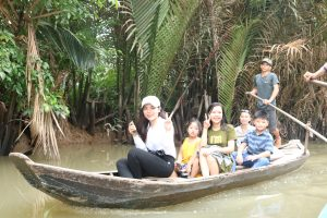 Đoàn di chuyển trong rạch nhỏ bằng xuồng chèo dưới rặng dừa nước xanh biết.