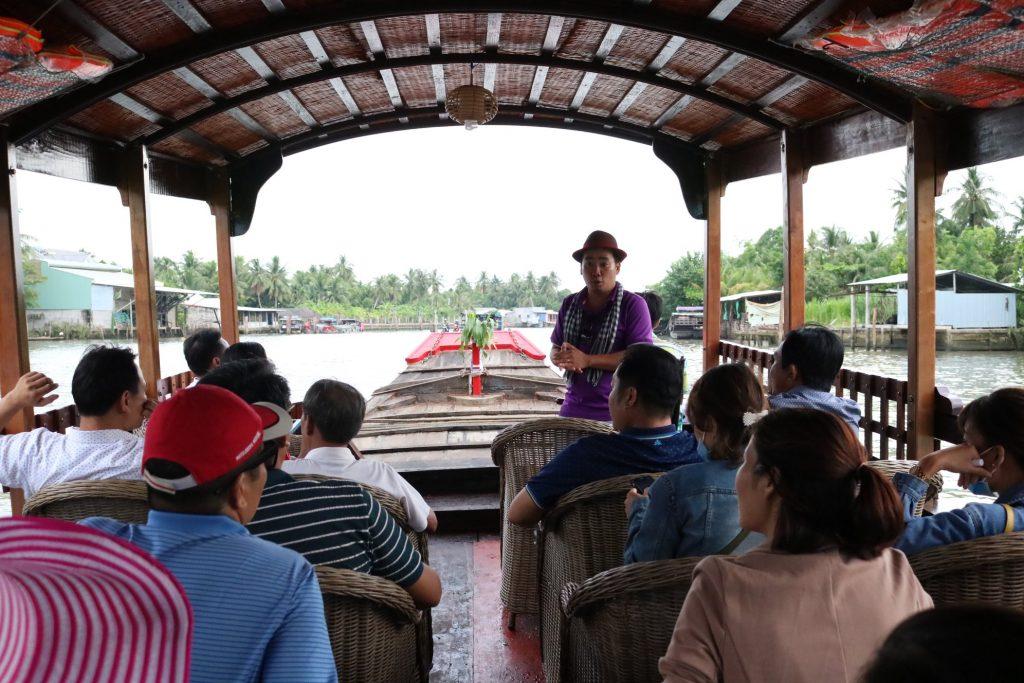 Du khách tham quan chợ dừa nổi song Thom trên thuyền